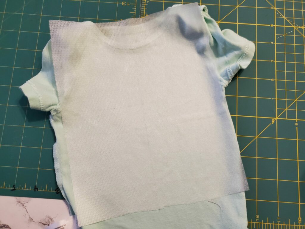 adhere cut-away or no show mesh stabilizer to the back of the onesie